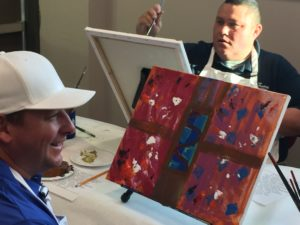 2 men during a collaborative painting session
